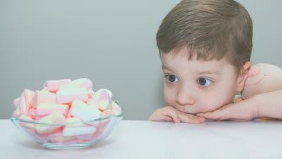Nein, jetzt noch nicht: Ein Bub praktiziert vor einer Schüssel Marshmallows die Kunst der Verzögerung. (Bild: Getty)