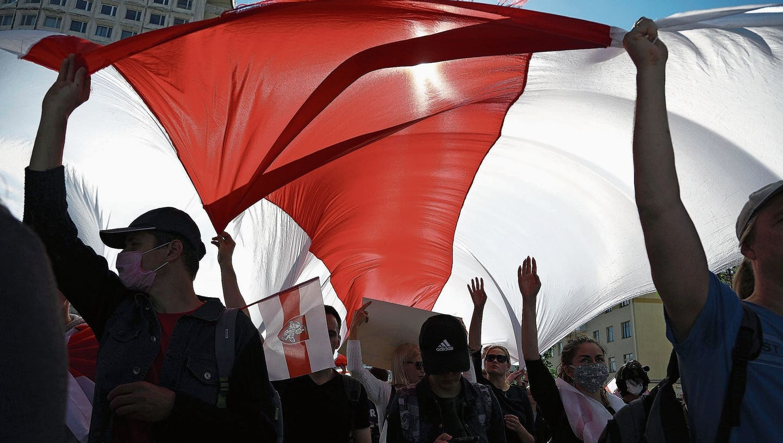 Ein Land, das nicht zur Ruhe kommt: Demonstranten tragen während einer Kundgebung der Opposition eine riesige alte belarussische Nationalflagge, um gegen die offiziellen Ergebnisse der Präsidentschaftswahlen zu protestieren. (Bild: AP/Keystone (Minsk, 13.September 2020))