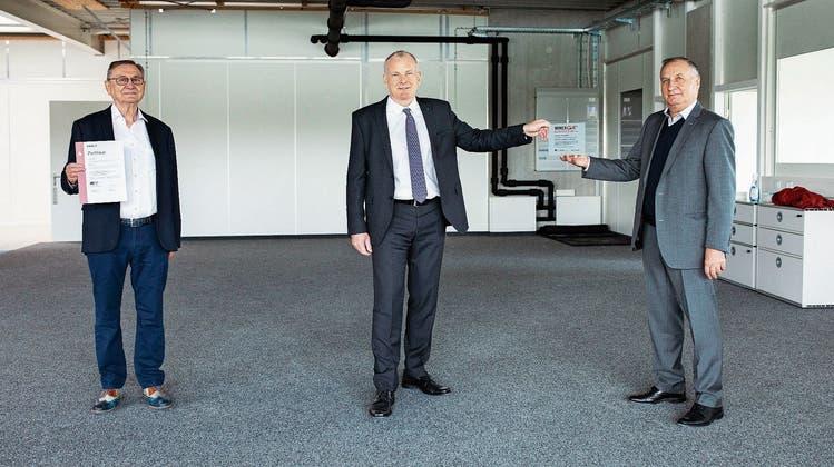 Landammann Stephan Attiger (M.) überreichte das Zertifikat an Hans Huber (r.) und Werner Hauri von der Quellmatten AG. (Bild: Britta Gut)
