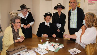 Referenten und Gäste der Sonderausstellung im Schloss Arbon spielen zusammen am Tisch. (Bild: Hedy Züger)