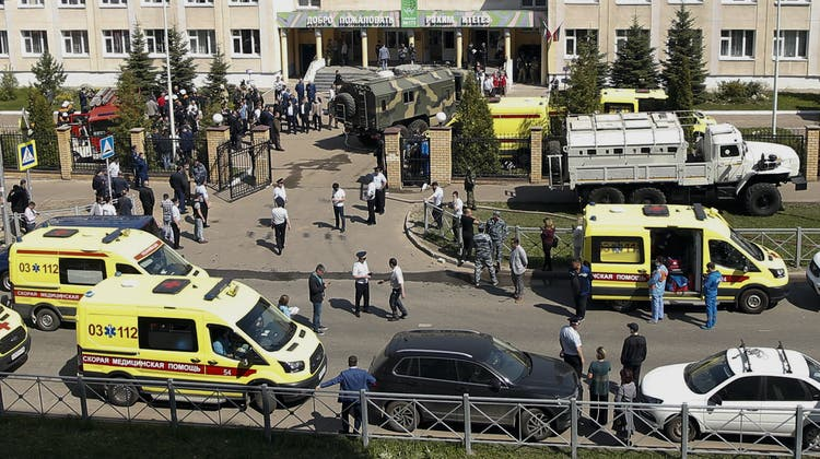 Firefighters walk past ambulances and police cars and a truck parked at a school after a shooting in Kazan, Russia, Tuesday, May 11, 2021. Russian media report that several people have been killed and wounded in a school shooting in the city of Kazan. Russia's state RIA Novosti news agency reported the shooting took place Tuesday morning, citing emergency services. (AP Photo/Roman Kruchinin) (Roman Kruchinin / AP)