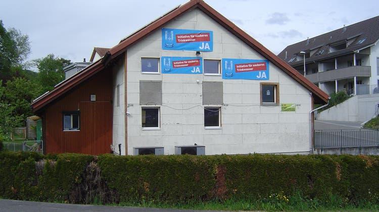 Mit einer Hebebühne hat Christian Lüthi die neuen Plakate an seinem Haus im oberen Fassadenbereich angebracht. (Bild:zvg)