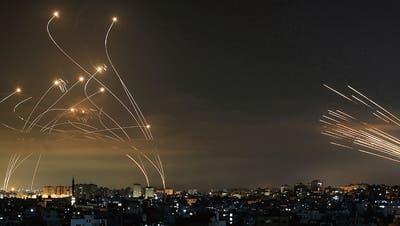 Tödliches Schauspiel am Tel Aviver Nachthimmel: Die Hamas schiesst Raketen aus dem Gazastreifen nach Israel (rechts), Israel lässt Abfangraketen steigen (links). (Bild: Anas Baba/AFP)