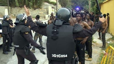 Polizisten der spanischen Guardia Civil drängen Migranten zurück. (Keystone)