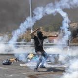 Ein Palästinenser schleudert ein Tränengas-Geschoss zurück in Richtung israelischer Armee: Der gewaltsame Konflikt lässt sich durch Joe Bidens Versuch der Deeskalation nicht überwinden. (Nasser Nasser / AP)
