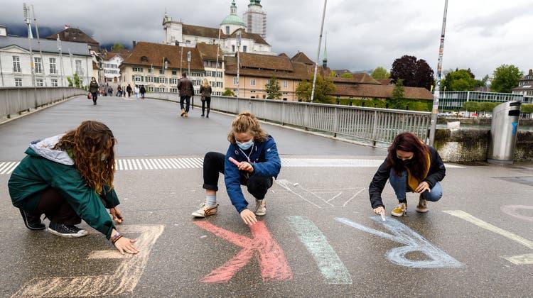 Aktivistinnen des Klimastreiks malen auf dem Kreuzackerplatz mit Kreide. (Hanspeter Bärtschi)