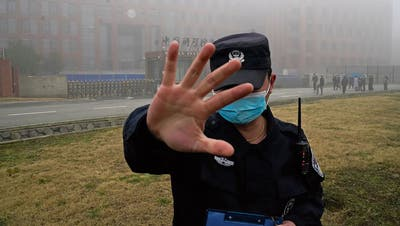 Ein Sicherheitswärter hält Journalisten vor dem Wuhan Institute of Virology(WIV) zurück. Hintenerhält eine Delegation der WHO Zutritt.