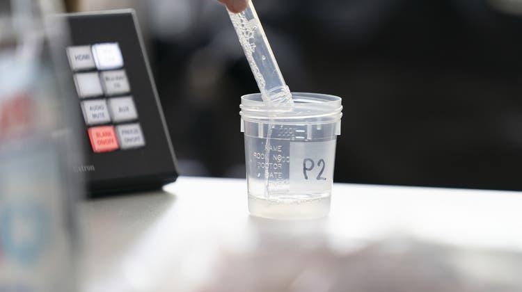 Die Speichelproben werden über ein Röhrchen in einen Behälter abgegeben. (Gaetan Bally / Key)