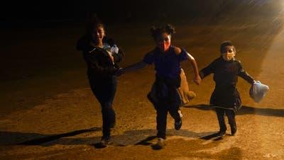 Drei Kinder im Grenzort Roma, Texas: Sie überquerten die Grenze in die USA, jetzt befinden sie sich in einer Auffangzone der Grenzwächter. Die Zahl der unbegleiteten Jugendlichen steigt rasant. (Foto: Gregory Bull / AP)