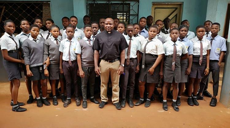 Pfarreiadministrator Augustine Asogwa aus Sarmenstorf gemeinsam mit Schülern in Nigeria. (zvg)