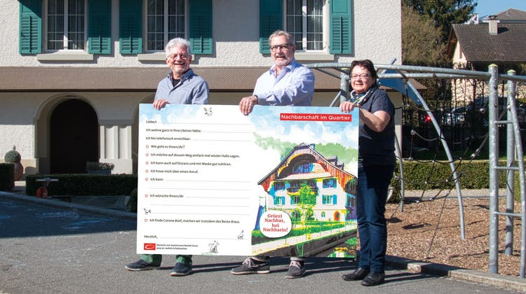 Der Vorstand des Quartiervereins Neufeld zeigt eine übergrosse Nachbarschaftskarte, die in vielen Geschäften in Sursee gratis abgeholt werden kann. (Bild: Paul Zinniker)