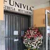 Der Blumenkranz am Eingang zur Talstation der Seilbahn: Gespendet wurde er von den Verantwortlichen des Giro d'Italia, der am Freitag den Ort passiert hat - aus Pietätsgründen ohne kleinen Bergpreis auf den Mottarone. (Dominik Straub)