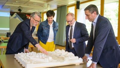 Kantonsbaumeister Michael Fischer, Regierungsrätin Susanne Hartmann, RegierungsratStefan Kölliker und Gemeindepräsident Alois Gunzenreinerbeugen sich über das Modell. (Michel Canonica)