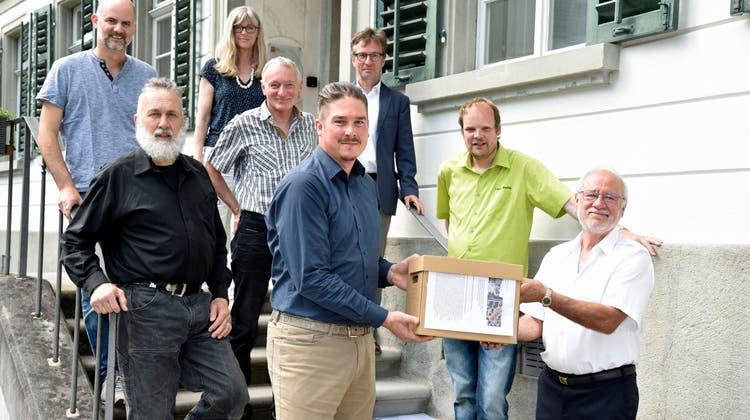 Stadtschreiber Reto Marty (Mitte) nimmt die Unterschriftenbögen des Initiativkomitees vor dem Stadthaus entgegen. (Bild: Mario Testa)