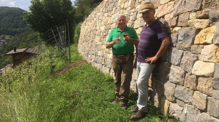 Projektleiter Rudolf Thommen (links) und Trockensteinmaurer Dieter Schneider stossen auf das «Jahrhundertwerk» an. (Simon Tschopp)