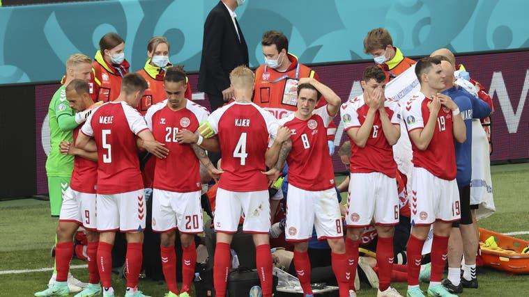 Die dänische Mannschaft formt einen Kreis um Christian Eriksen, der von Ärzten und Sanitätern betreut wird. (Keystone)