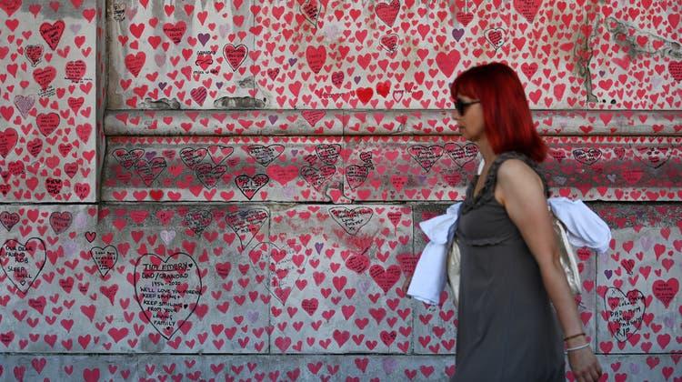 Die grossen Öffnungen wurden wegen der Delta Variante in England um vier Wochen verschoben. Eine Frau geht in London an der Corona-Memorial-Wand vorbei. (Bild: Andy Rain/EPA)