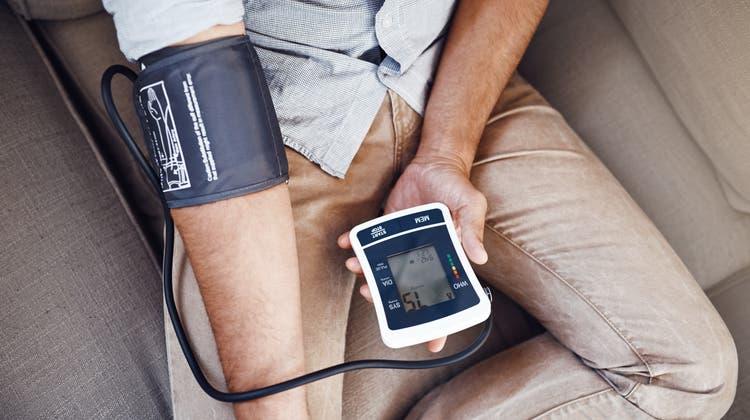 Ein Mann misst seinen Blutdruck. (Bild:Getty Images)
