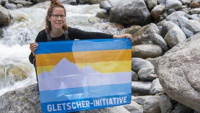 Myriam Roth, Co-Präsidentin des Vereins Klimaschutz, posiert am Tag der Hommage an die Gletscher mit einer Fahne. Schon bald sollen 100'000 dieser Flaggen zur Gletscherinitiative bis in die hintersten Winkel der Schweiz zu sehen sein. (Bild: Keystone (Trient VS, 6. September 2020))