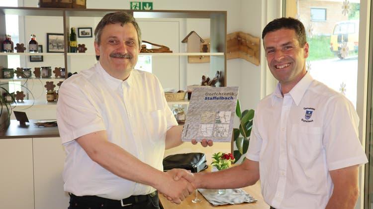 Markus Widmer-Dean übergibt die Chronik an Gemeindeammann Max Hauri. (Peter Weingartner / Aargauer Zeitung)