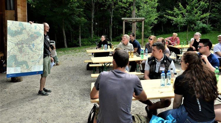 Gemeinderat Peter Meier zeigt den Eschliker Neuzuzügern die überarbeitete Freizeitkarte. ((Bild: Christoph Heer))