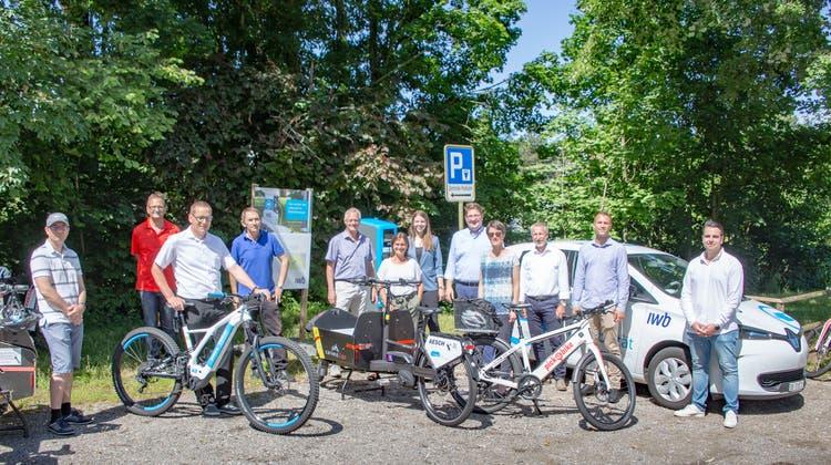 Vertreter der Gemeinden Aesch und Pfeffingen sowie der beteiligten Unternehmen posieren hinter den neuen Fahrzeugen und vor der frisch erstelltenIWB-Ladesäule. (Joël Gernet)