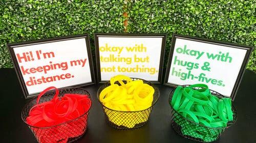 Kommen in ausländischen Firmen nach der Rückkehr aus dem Home Office vermehrt zur Anwendung: Bunte Gummi-Armbänder mit unterschiedlichen Social-Distancing-Anweisungen. Auch US-Hochzeits-Organisatoren bieten die Bändelifür Gäste an. (Screenshot, Boxwoodrose.com)