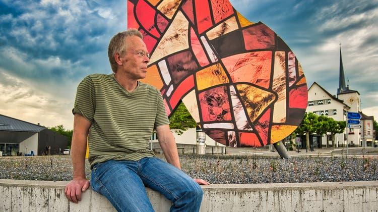 Kunstglaser Daniel Hebeisen sitzt vor dem Bassisten im Pentorama-Kreisel, dem er zwei neue Kleider verpasst hat. Von Osten her kommend ein rotes, von Westen her kommend ein blaues. (Bild: Manuel Nagel (Amriswil, 22. Juni 2021))