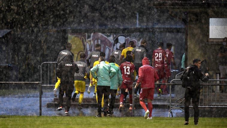 Rette sich, wer kann! Spieler, Trainer und Schiedsrichter flüchten vor dem Unwetter ins Garderobengebäude. (Alexander Wagner)