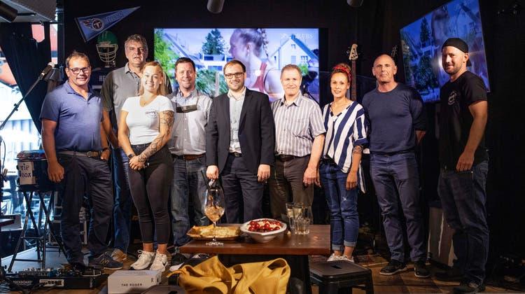 Hier erhält Dano Dreyer, Mitinhaber der neuen «Henry's»-Bar in Baden, ein Trikot des ehemaligen Radprofis Tony Rominger (mit Mikrofon). (Bilder: Britta Gut)