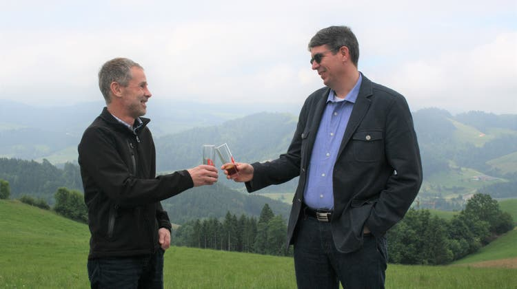 Auf der Grenze der Schulgemeinden Schlatt und Haslen (beim Bädli Leimensteig) stossen die Schulratspräsidenten Andreas Fuchs und Marc Rechsteiner mit «Appenzeller» auf das klare «Ja» zum Fusionsvertrag an. (Bild: VP)
