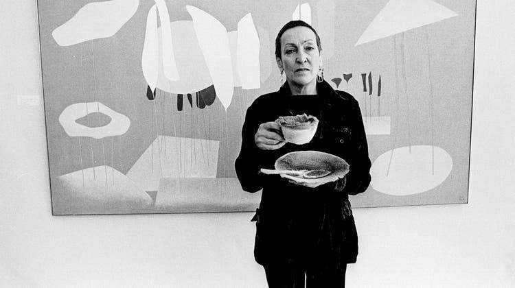 Meret Oppenheim 1972 bei der Eröffnung ihrer Ausstellung in Duisburg mit der «Pelztasse» von 1936. (Quelle:akg-images / Brigitte Hellgoth / © 2021, ProLitteris, Zurich.)