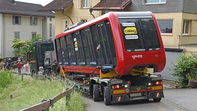Die Herstellerfirma Stadler Rail in Bussnang ht gestern den ersten von insgesamt 8 bestellten neuen Triebwagen der Pilatus-Zahnradbahn nach Alpnachstd geliefert. Hier wird er einem Testprogramm unterzogen. Der Wagen wurde mit einem Sattelschlepper über den engen Pilatusweg ins Depot oberhalb der Talstation transportiert.Die neuen Triebwagen sind Bestandteil des 55-Millionenprojektes Neukonzeption der Pilatus-Zahnradbahn. Der zweite neue Wagen wird 2022 geliefert und ab Mai 2023 die restlichen bestellten sechs Wagen. Sie ersetzten die bisherigen Wagen aus den 1930er-Jahren und bieten Platz für 48 Passagiere.Bild: Rüclwärtsfahrt in Alpnachstad auf dem schmalen Pilatusweg zum Dept.Bild Robert Hess (Alpnachstad, 7. Juni 2021) (Robert Hess / Obwaldner Zeitung)