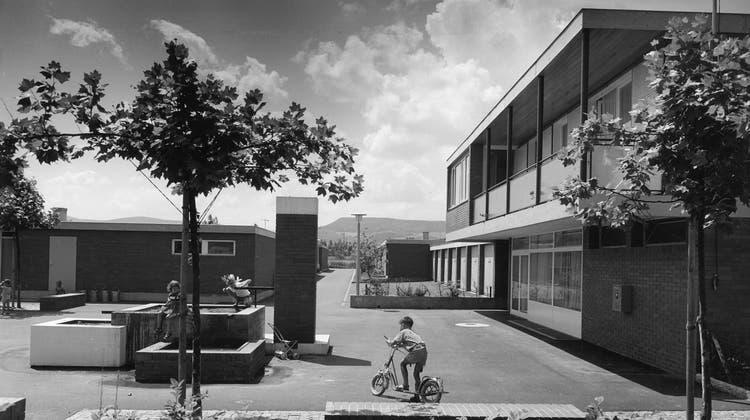 Ein Klassiker der Moderne: eine der Einfamiliensiedlungen. In den Gartenhöfen in Reinach ermöglicht die verwinkelte Architektur den Rückzug ins Private. Zugleich betont der Dorfplatz (im Bild aus dem Jahr 1961) das Gemeinschaftliche. (Ulrich Löw/Theodor Manz)