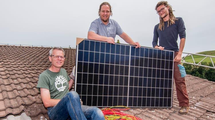 Samuel Kretzschmar (links) ist auf den Geschmack von körperlicher Arbeit gekommen.Florin Schaffner (Mitte), Geschäftsführer der Energiewendegenossenschaft Basel, und Projektleiter Dominic Müller unterstützen ihn bei der Installation einer Solaranlage. (Nicole Nars-Zimmer)