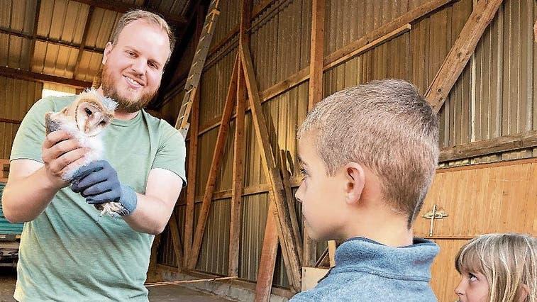 Dominic Frei zeigt den Kindern einen Schleiereulennestling.