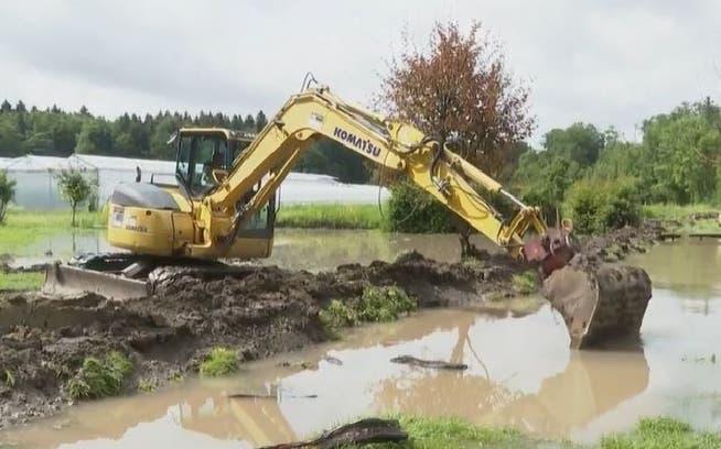 Biobauer Lukas Neuhaus aus Stetten baut einen provisorischen Damm, um seine Felder vom Wasser der Reuss zu schützen.