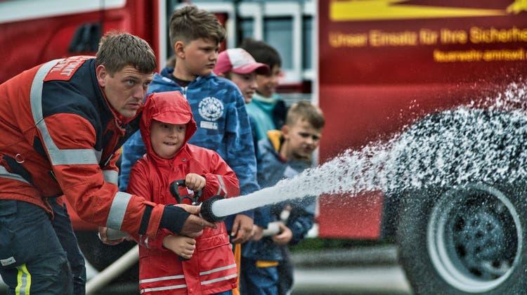 OffizierThomas Haag zeigt den Kindern, wie man einen Feuerwehrschlauch benutzt. (Bild: Manuel Nagel)