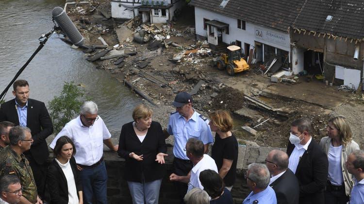 Bundeskanzlerin Angela Merkel (3.v.l hinten CDU) und Malu Dreyer (5.v.l hinten, SPD), Ministerpräsidentin von Rheinland-Pfalz, sprechen mit Helfern und Betroffenen bei ihrem Besuch in den vom Hochwasser verwüsteten Schuld bei Bad Neuenahr-Ahrweiler. (Christof Stache / POOL AFP)