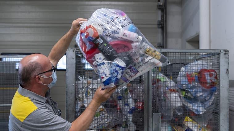 Ein Pöstler deponiert in der Reinacher Post eineneingesammelten Sack mit Kunststoff. (Georgios Kefalas / Keystone (25. Juni 2021))