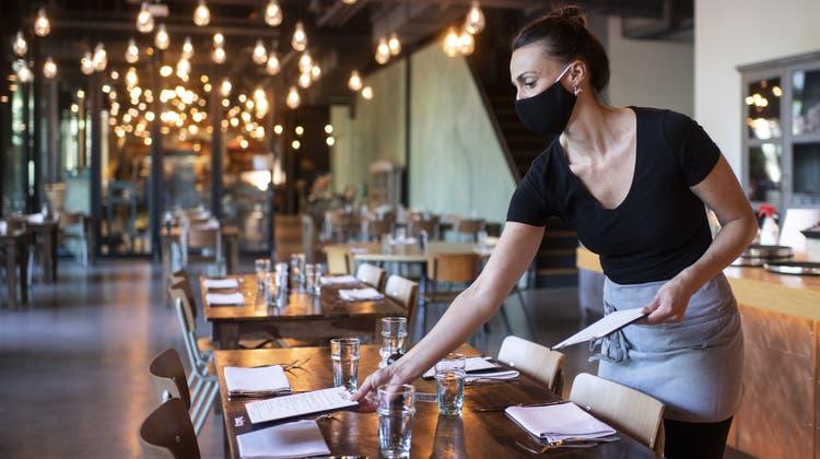 Eine Serviceangestellte deckt in einem Restaurant den Tisch. (Keystone)