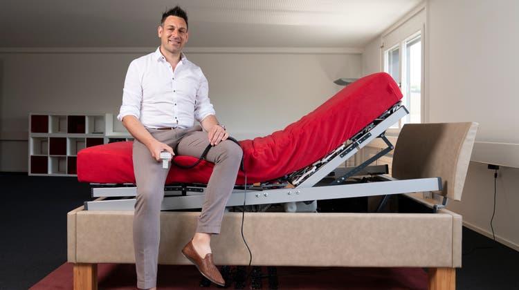 Smarte Lösung: Reto Schmid auf seiner Erfindung. Das Hubantriebssystem kann in jedes herkömmliche Bett eingebaut werden. (Bild: Claudio Thoma)