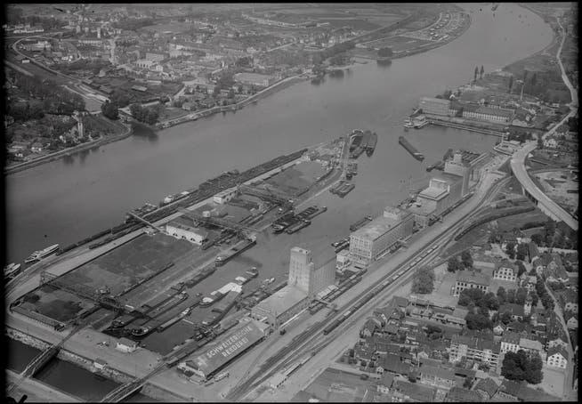 1906 begann in Basel der Bau des Hafens. Das Bild stammt von 1948. Auf der Innenseite des Hafenbeckens I befinden sich die Getreidesilos der führenden Rheinschifffahrtsfirmen. Auf der Aussenseite gegen den Rhein dominiert der damalige Hauptenergieträger, die Kohle.