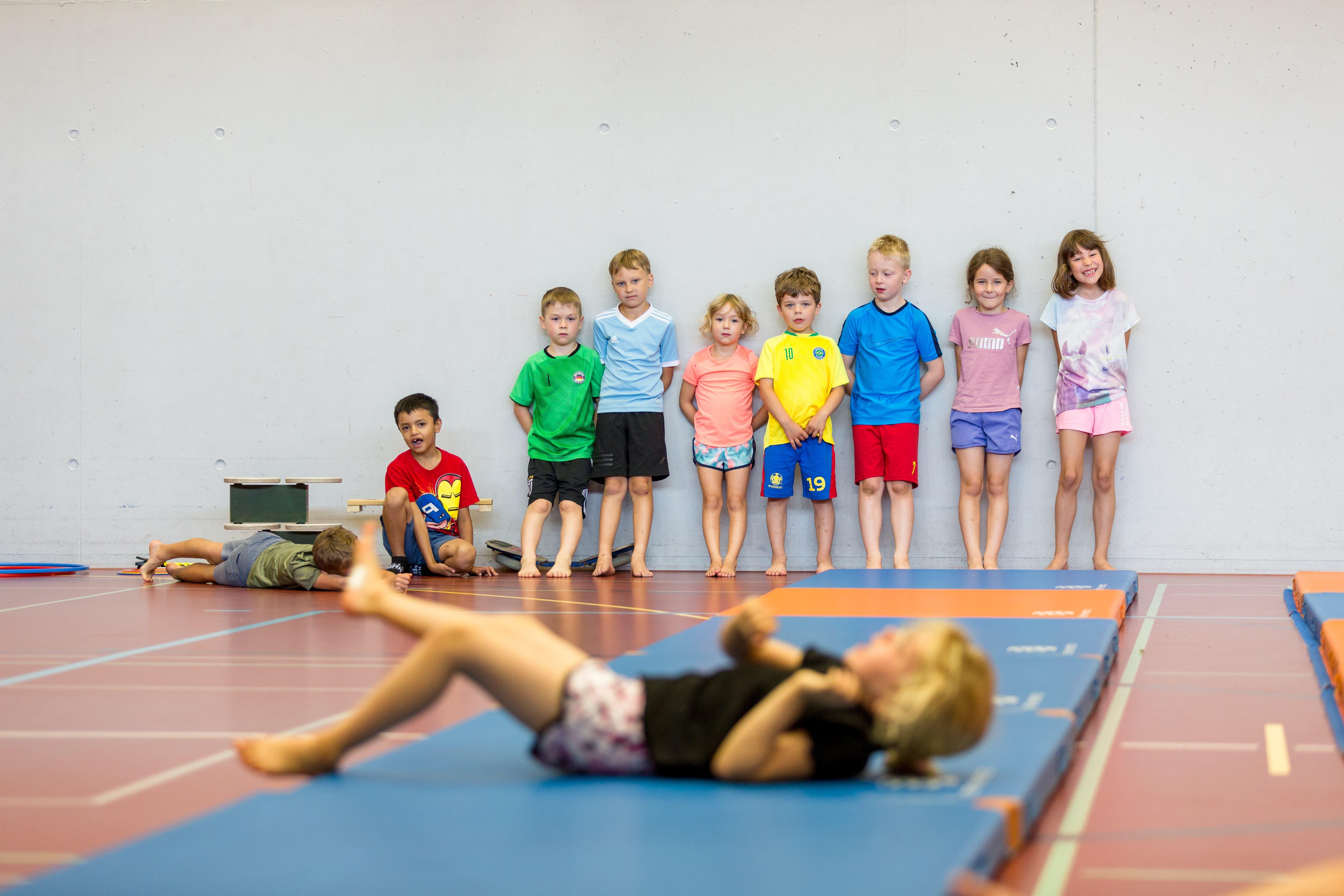 Richtiges Aufwärmen ist wichtig: Die Kinder rollen über die Matte und sollen dabei die Körperspannung trainieren.