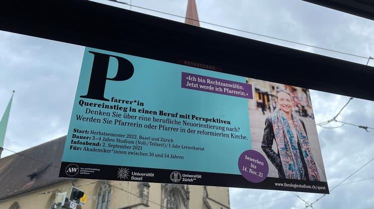 Plakat in einem Basler Tram – fotografiert vor der Heiliggeistkirche. (Nora Bader)