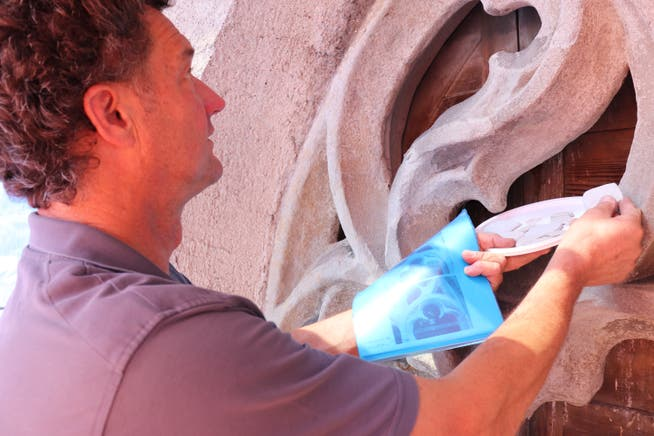 Tobias Hotz schaut, welches Füllmaterial farblich am besten zum Originalfenster passt.