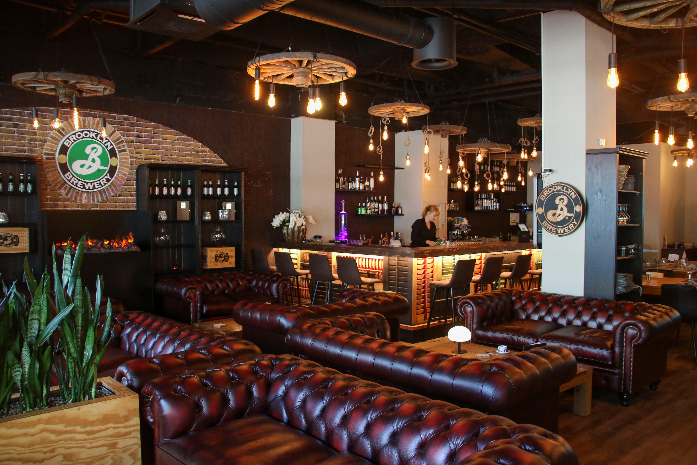 Die wuchtigen Ledersofas im Loungebereich des «Bones» sind ein Blickfang. Dahinter steht Franziska Regli an der Bar.