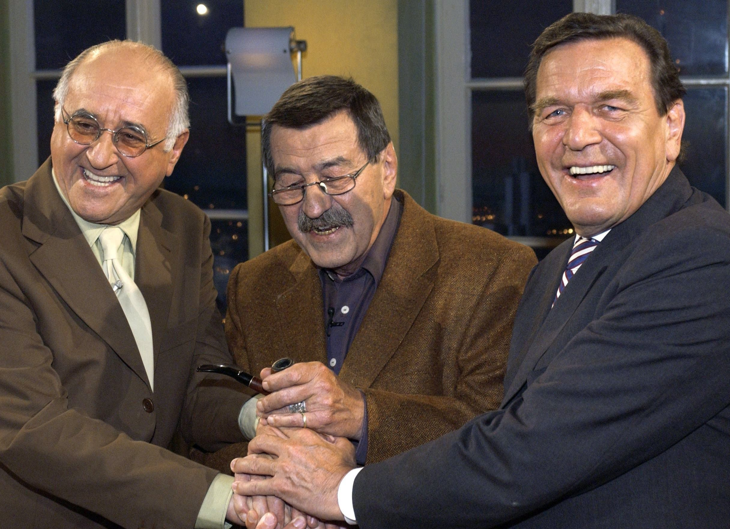 """Gerhard Schröder (SPD, r-l), damals Bundeskanzler, der Schriftsteller Günter Grass und Moderator Alfred Biolek geben sich nach einer Aufzeichnung von """"Boulevard Bio"""" die Hand. (Archivbild von 2002)"""