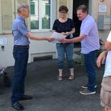 Blumenrain-Anwohner Ake Strinning (links) übergibt Gemeindeammann Hans Rätzerund Gemeindeschreiberin Nicole Wernli die Petition. (Florian Wicki)