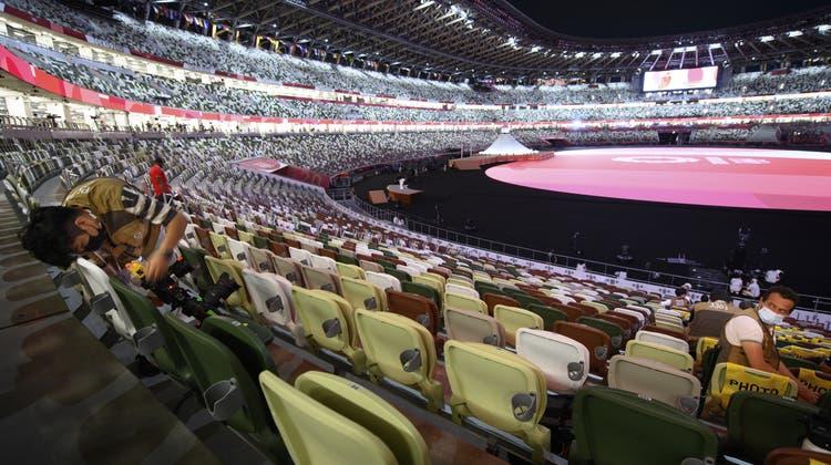 Einzelne Medienvertreter aber ansonsten leer: Das Nationalstadion kurz vor Beginn der Eröffnungsfeier für die olympischen Spiele. (Keystone)